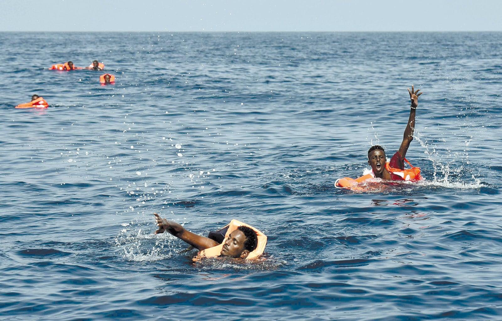 Immigrants subsaharians demanen ajuda a un vaixell de rescat al mar Mediterrani. ©Aris Messinis/AFP