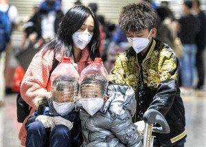Uns nens amb-garrafes d'aigua com a improvisada protecció a l'aeroport de Guanzhou, Xina. Fotografia d'Alex Plavevski. EFe