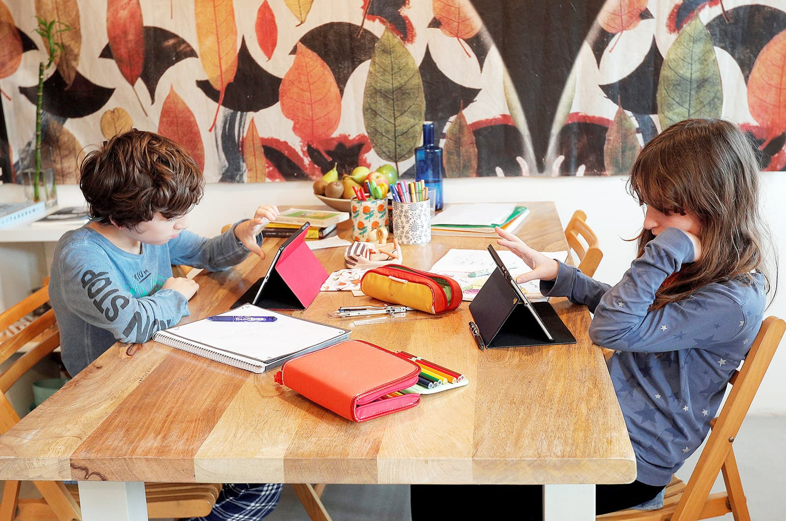 Dos nens de primària fan les tasques escolars, durant el confinament, a casa seva a Godella, València. Fotografia de Kai Försterling. Efe