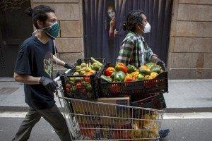 Dos voluntaris de la Xarxa Popular d'Aliments del Raval fan un recorregut pels comerços del barri per recollir donatius. Fotografia de Sira Esclasans.