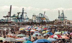 Platges plenes de turistes amb el port de València al darrere, el 2019, dues de les indústries principals de la Comunitat Valenciana. Fotografia de Manuel Bruqué. Efe.