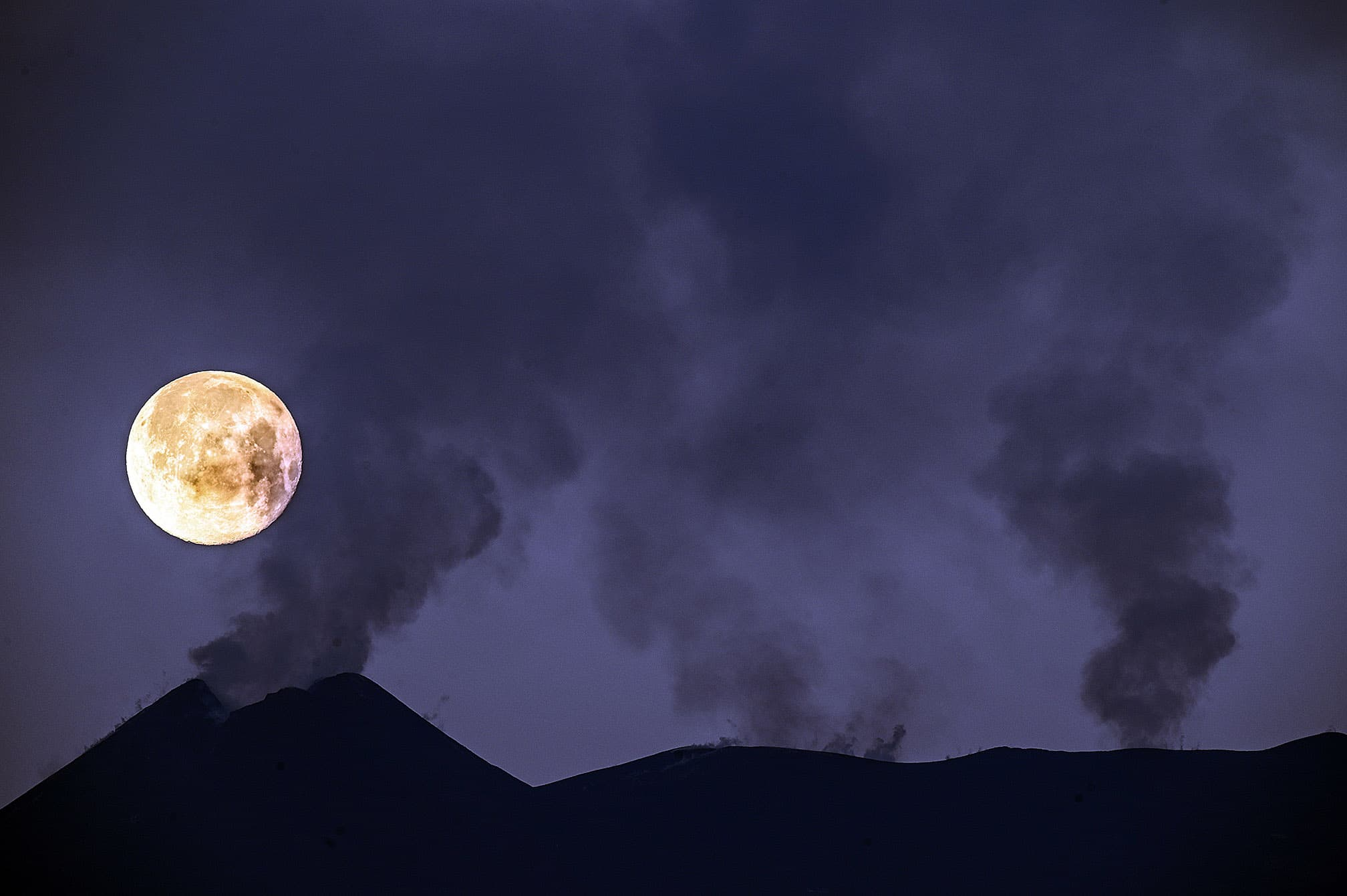 La lluna plena al darrere de les fumaroles del cràter sud-est de l'Etna, el 28 de febrer. Fotografia de Fabrizio Villa. Getty Images.