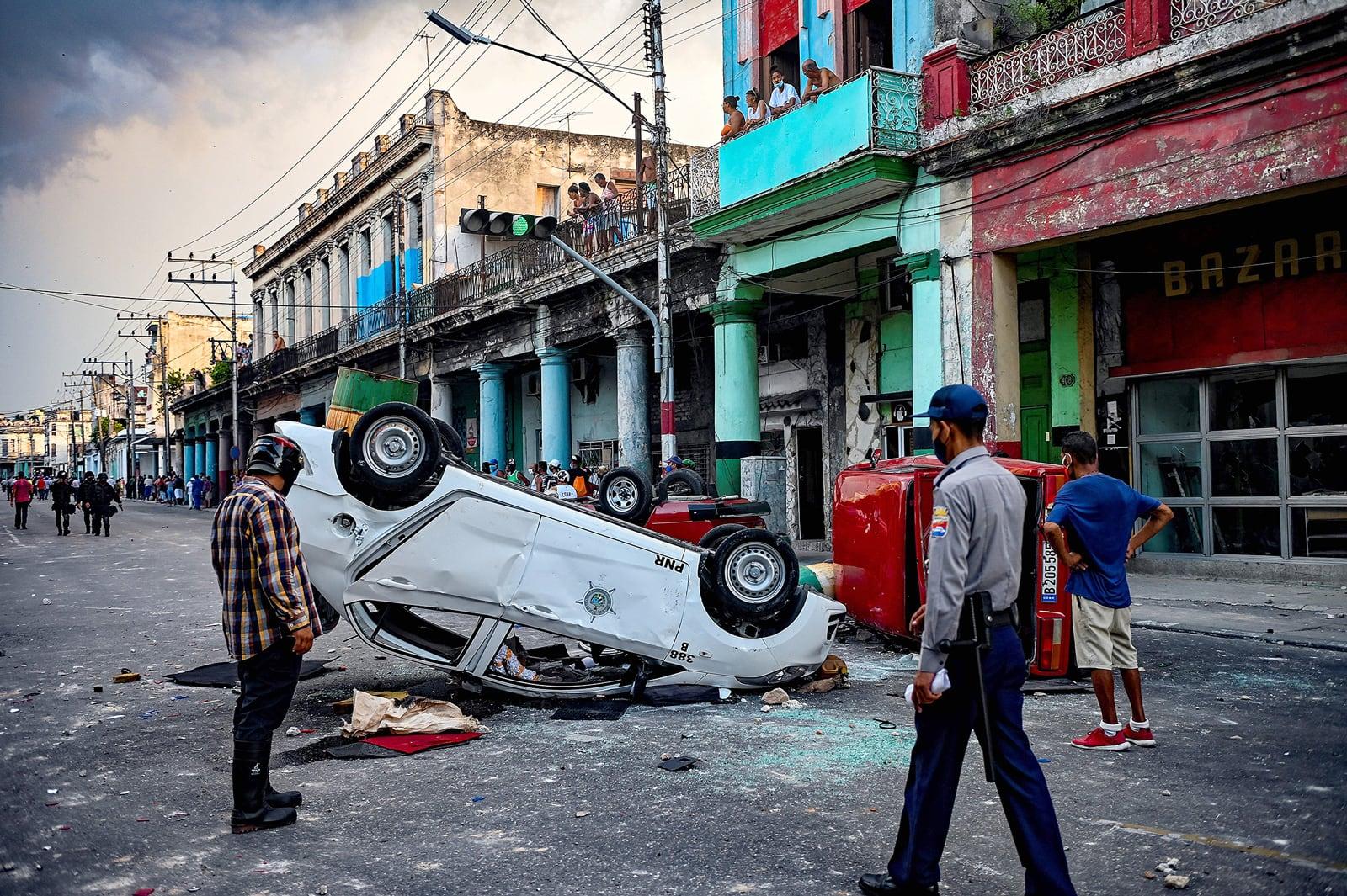 Cotxes de la policia bolcats a l'Havana, l'11 de juliol, durant les protestes contra el president Miguel Díaz-Canel i el govern comunista. Fotografia de Yamil Lage. AFP. Getty Images.